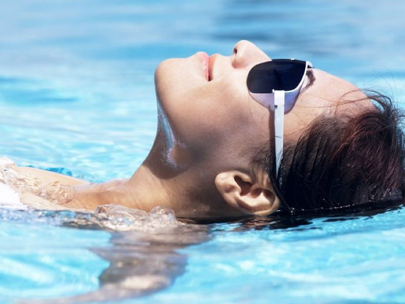 14684017-Beautiful-young-asian-woman-resting-in-the-swimming-pool-on-the-sunny-day--Stock-Photo